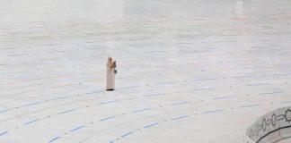 Hajj - une femme invoque seule devant une Kaaba généralement bondée