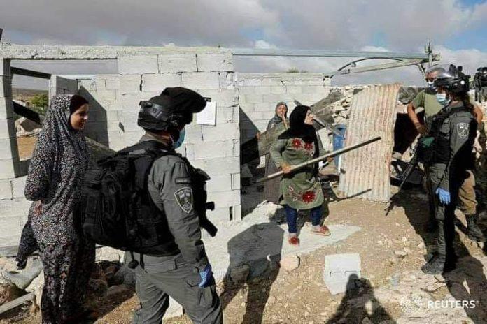 Hébron - une femme palestinienne affronte les forces israéliennes avec un bâton les empêchant de démolir sa maison