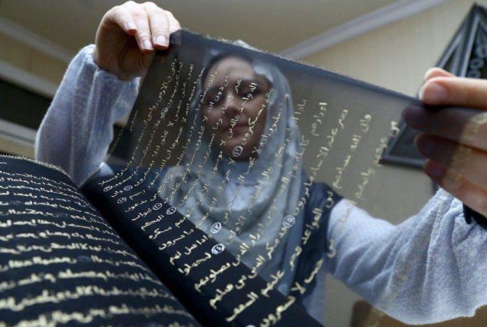 Une femme brode à la main une copie entière du Noble Coran sur de la soie pure